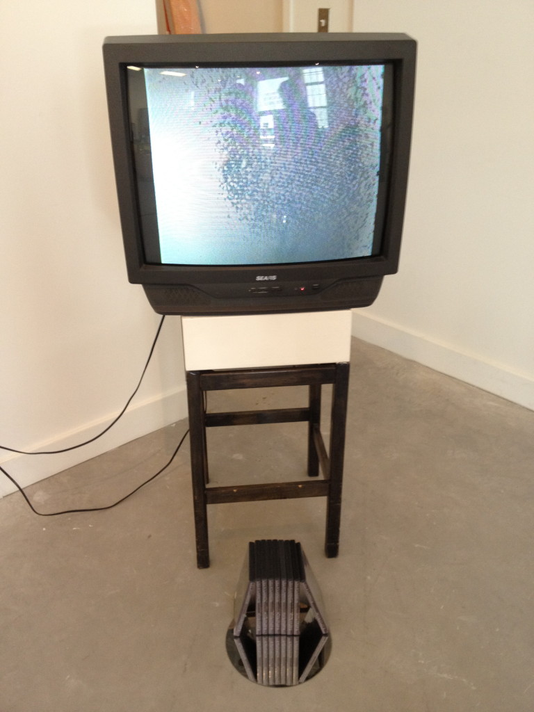 An installation shot of the video on a television on a plinth with DVDs in front